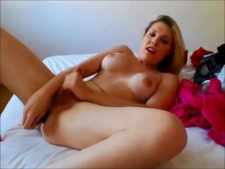 Blonde shemale pleasing herself on her bed